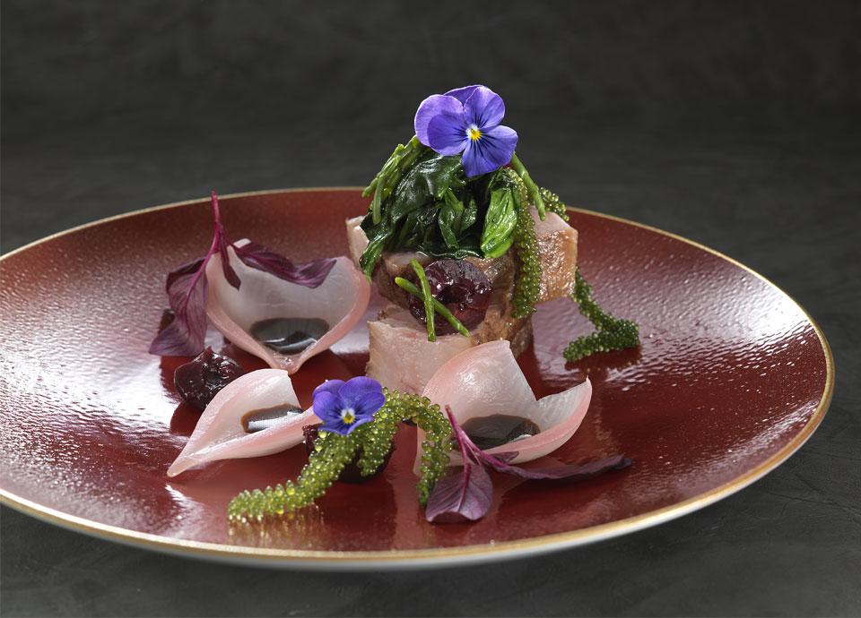 昆布の旨みをまとった鹿児島県産黒豚のロティ海ぶどうとダークチェリーをあしらったシェリービネガーソース